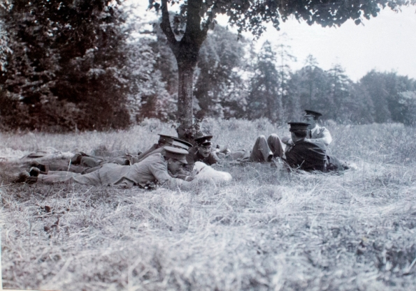 Officers lying in grass in shade of tree, compressed