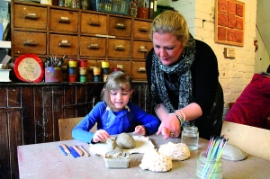 Coalport China Museum ceramic workshop, Sara Robinson helps a young visitor