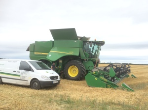Combine being fixed by the John Deere engineers